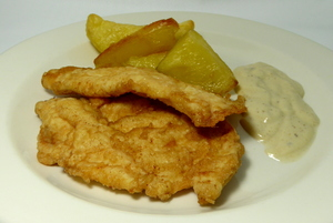 Battered turkey breasts with cheese sauce and baked potatoes