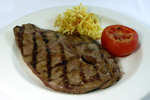 Grilled veal steak with baked tomatoes and chips