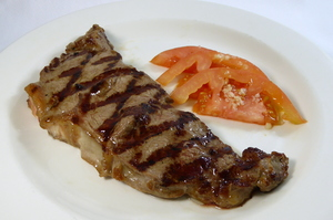 Grilled entrecôte with garlic and tomato salad