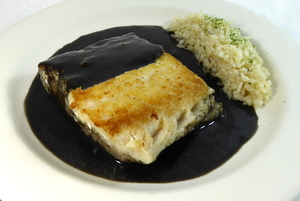 Hake in squid sauce with pilaw rice garnish
