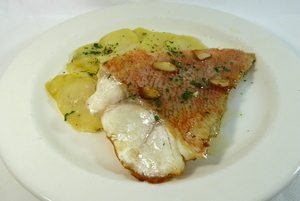 Roasted scorpion fish with baked potatoes and 'bilbayne' fried sauce
