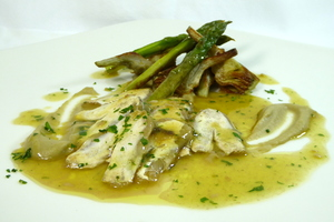 Hake chins with asparagus and artichokes in green sauce.