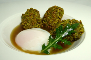 Chicken wings coated with pistachio crumbs and poached egg
