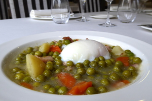Peas, carrot, potato and leeks stew with a poached egg.