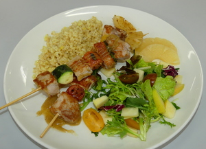 Brochetas de solomillo de cerdo con arroz integral al curry Thai y ensalada.