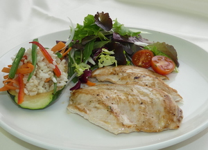Chicken breast fillets with salad and courgette filled with rice and vegetables