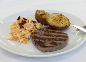 Beefburger with baked potato and coleslaw with carrots and apple